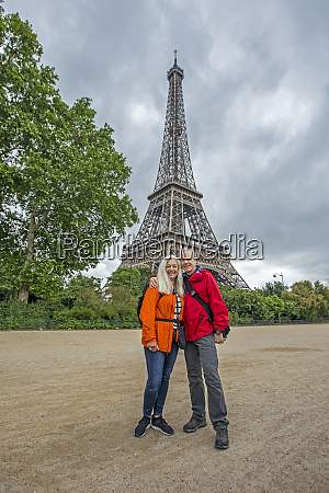 laechelndes paar am eiffelturm in paris