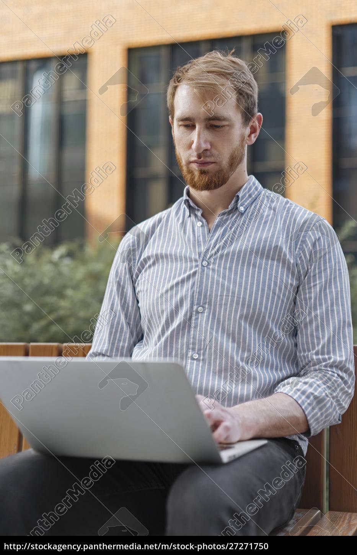bearded, man, using, laptop, outdoors - 27271750