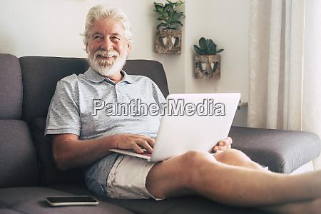 laechelnder senior mann mit laptop auf