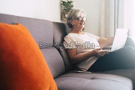 laechelnde seniorin mit laptop auf sofa