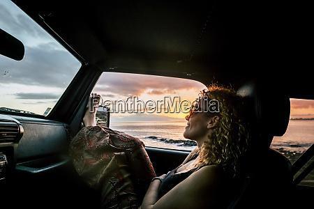 frau im auto mit erhobenen beinen