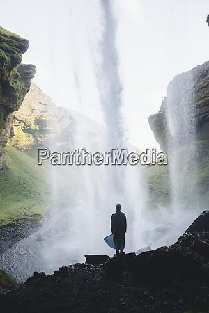 silhouette des menschen hinter kvernufoss wasserfall