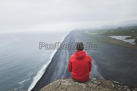 mann im roten mantel sitzt ueber