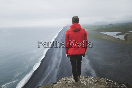 mann traegt roten mantel ueber strand