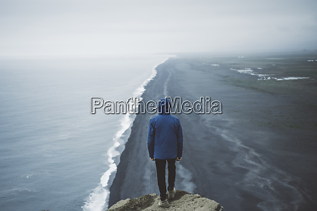 mann traegt blauen mantel ueber strand
