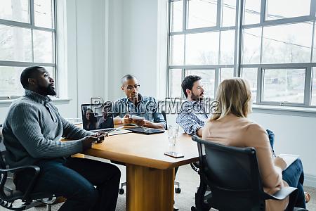 mitarbeiter im sitzungssaal beim videoanruf
