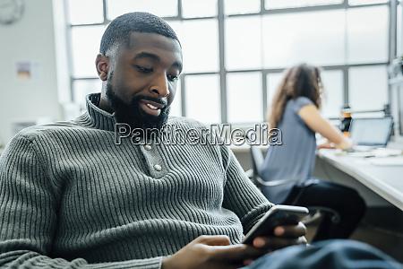 mann mit smartphone im buero
