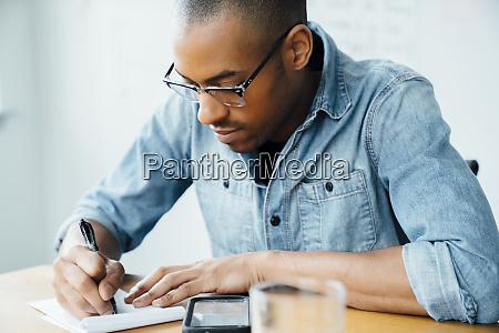 mann traegt brille die auf notizblock