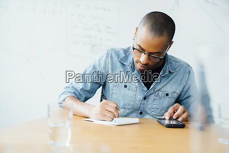 mann mit smartphone beim schreiben auf