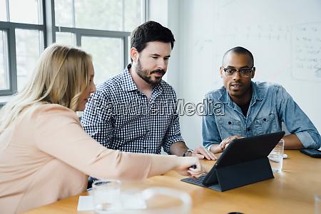 mitarbeiter mit digitalem tablet im sitzungssaal