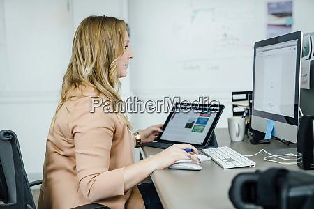 frau mit digitalem tablet und computer