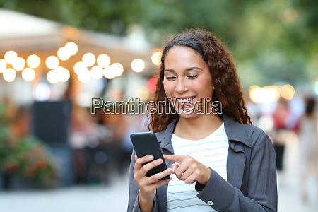 glueckliche gemischte rasse frau mit smartphone