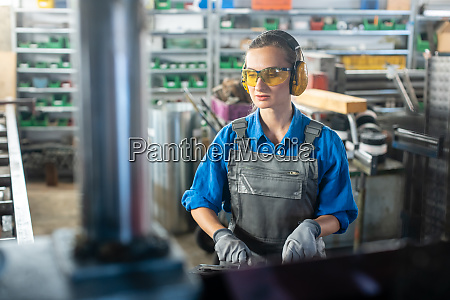 arbeiterin die eine werkzeugmaschine in einer