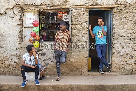 junge aethiopische maenner vor einem geschaeft