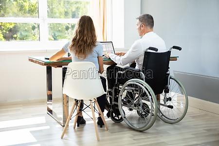behinderter geschaeftsmann sitzt mit seinem partner