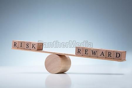 risiko und belohnung holzblock auf wippe