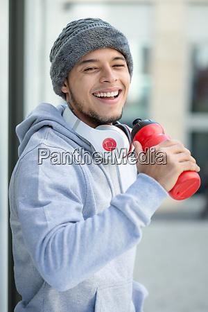 smiling young latin man drinking sports