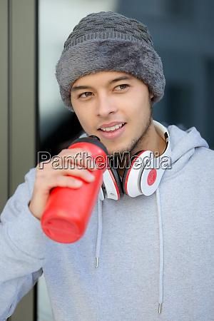 smiling young latin man drinking water