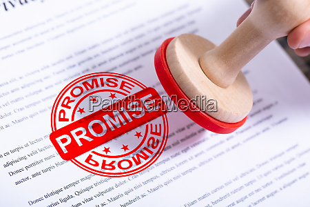 businessman putting promise stamp on document