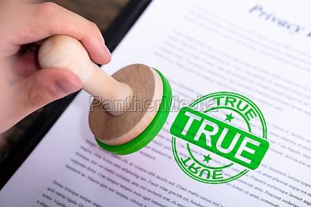 businessman putting true stamp on document