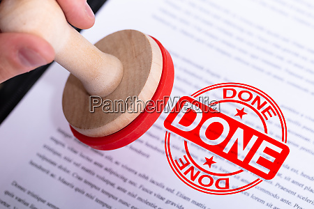 businessman putting done stamp on document