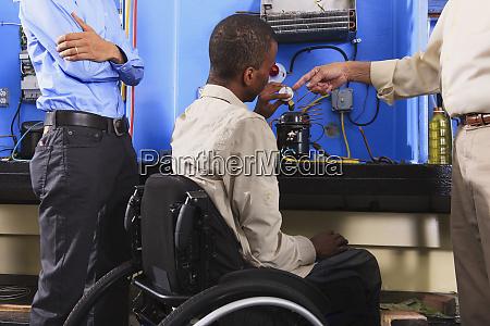 instruktor diskutiert kondensatorspule auf kaelteanlage mit