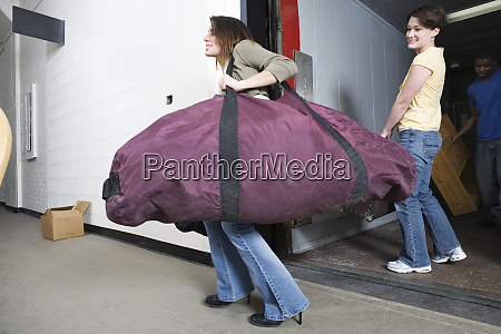 young woman carrying a huge traveling