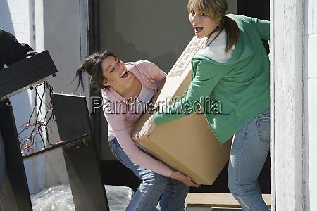women carrying box