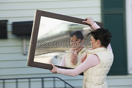 woman carrying mirror
