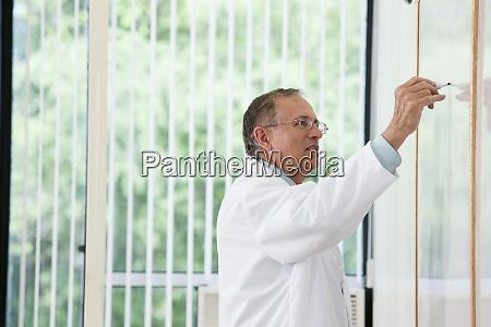 professor bei whiteboard waehrend vortrag