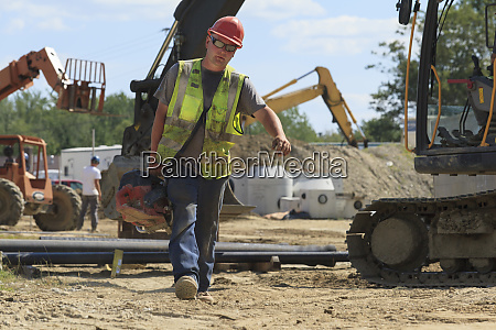 construction engineer carrying pipe cutting saw