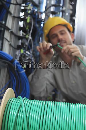 netzwerkingenieur schneidet kabelabschluss im netzwerk rechenzentrum