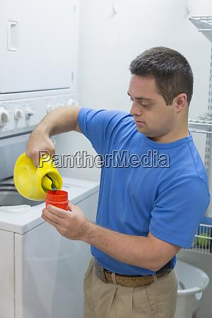 mann mit down syndrom giesst waschmittel