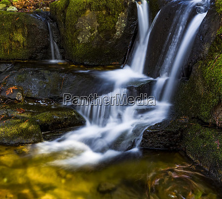 waterfalls with autumn coloured foliage on