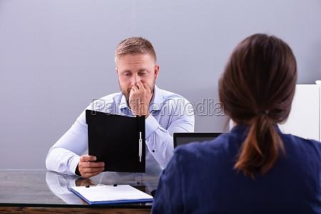 enttaeuschter junger mann sitzt beim interview