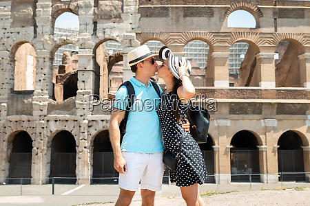 young couple kissing in front of