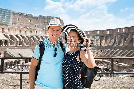 young couple standing inside of colosseum