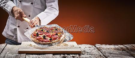chef in einer pizzeria mit hausgemachter