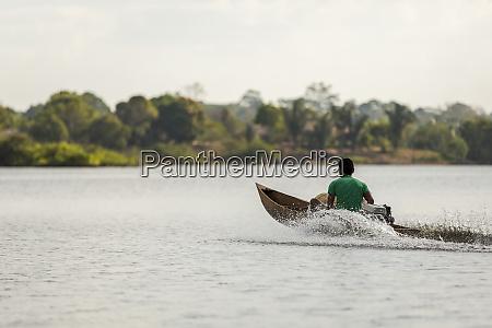 mann in einem motorisierten holz kanu
