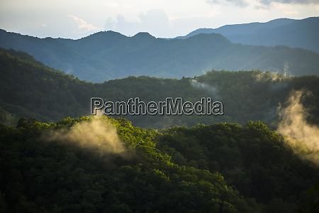 sunlight illuminates clouds along mountain ridges