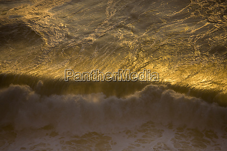 sunset on crashing surf along the