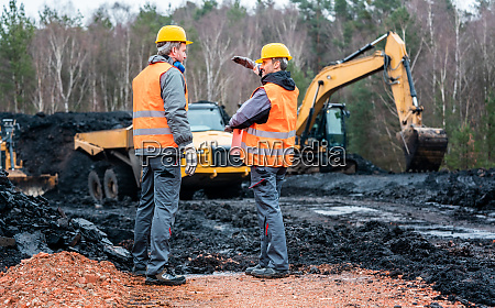 two quarry workers discussing what to
