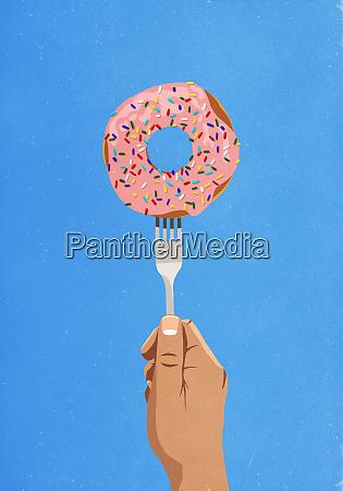 fork piercing donut with sprinkles