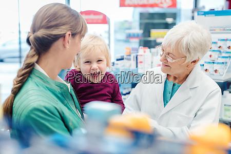 freundlicher apotheker mutter und kind mit