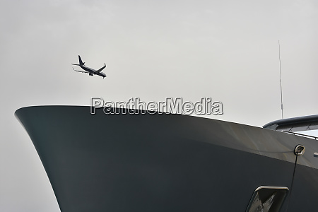 airplane flying over ship in overcast