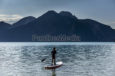 boy paddleboarding auf sonnigem idyllischem bergsee