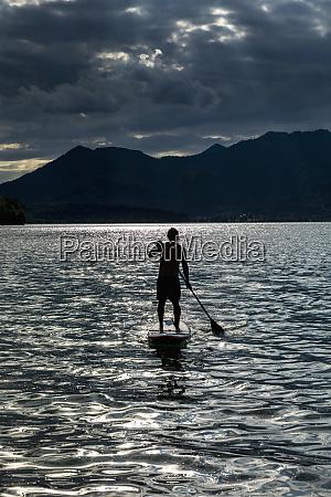 silhouette man paddleboarding auf sonnigem idyllischem