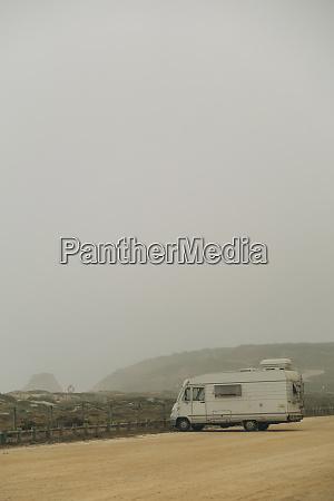 wohnmobil auf nebligen strandparkplatz geparkt santa