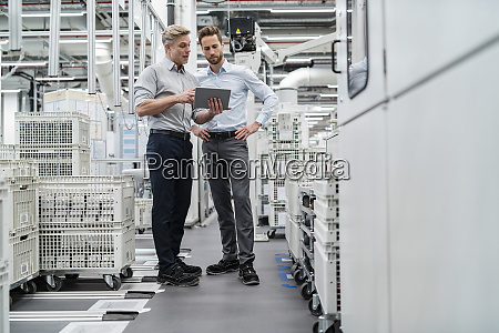 two businessmen with tablet talking in