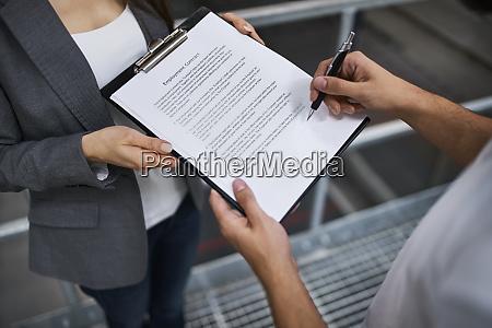 mann unterzeichnet arbeitsvertrag in fabrik von